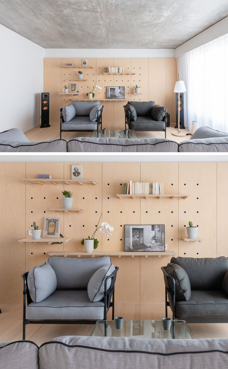 This modern apartment uses minimalist wood pegboard walls in the living room and master bedroom to create shelving for flexible displays and storage. #PegboardWall #Pegboard #InteriorDesign #Shelving