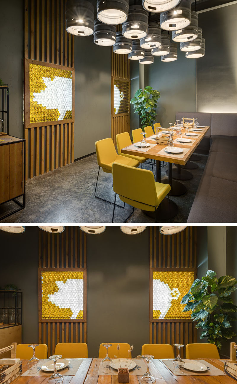 This modern brew pub and restaurant has a small private dining area with beer kegs that have been repurposed as lighting, while on the wall, decorative pig artwork is highlighted. #RestaurantDesign #Lighting #InteriorDesign