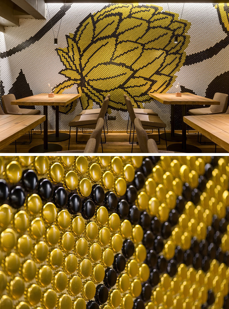 Drawing inspiration from the beer making process, a large wall mural in the form of a hop flower decorates the wall of this brew pub and restauant in silver, gold, and black. #Mural #RestaurantDesign #BarDesign