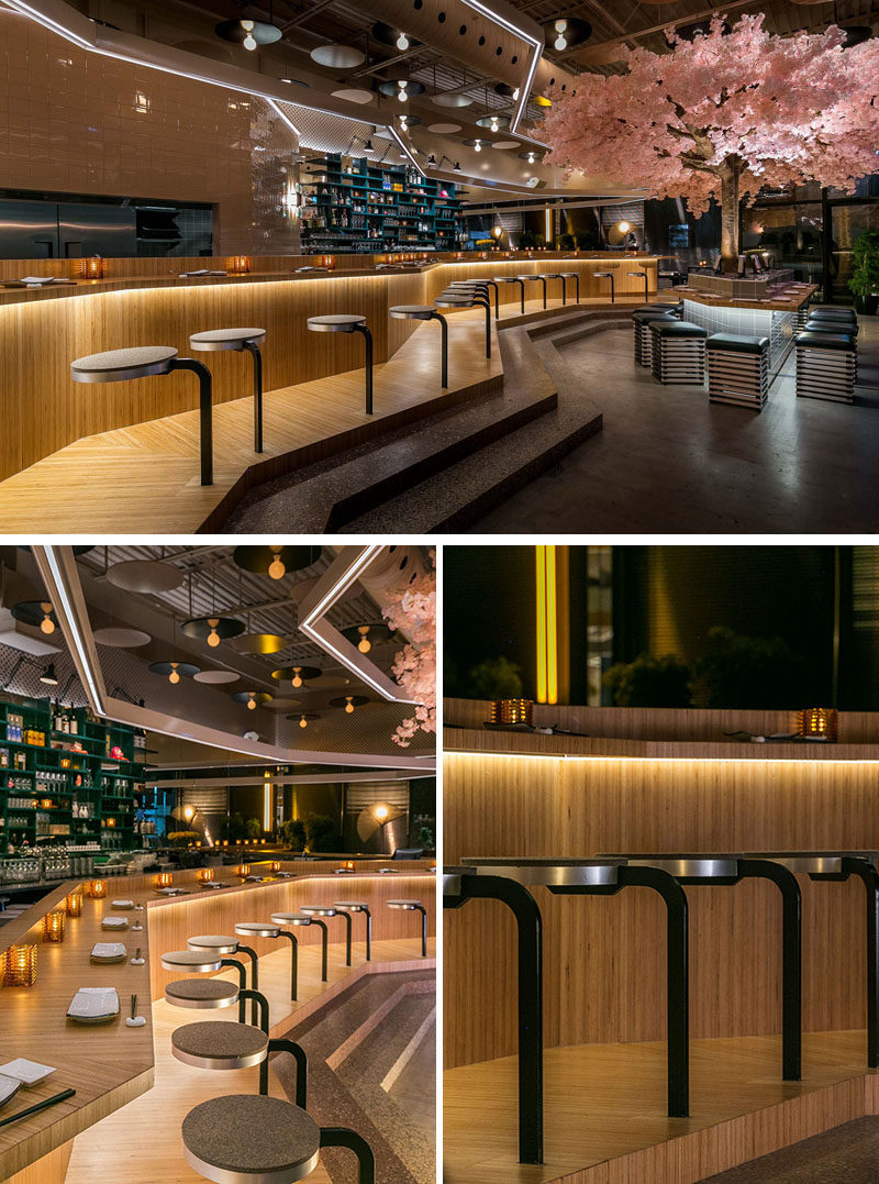 A large bar lined with stools runs the length of this modern restaurant. The European beech bar wasprefabricated and transported in six different parts, and is comprised of three distinct stations, set to accommodate the restaurant's three chefs. #RestaurantDesign #BarDesign #ModernRestaurant