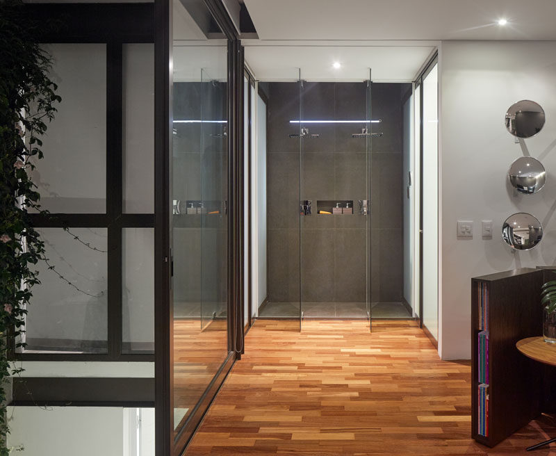 This master bedroom features an exposed glass enclosed shower. While, white doors on either side of the shower lead to the washroom and a walk-in closet. #Bathroom #GlassEnclosedShower