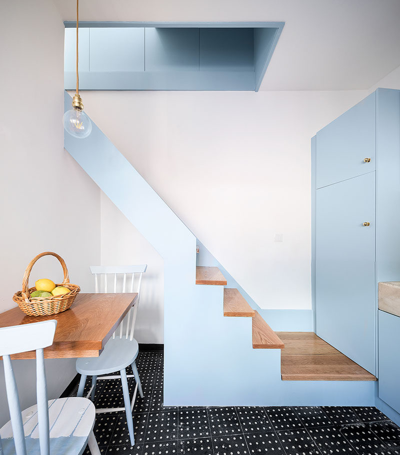 Simple stairs with wood treads run alongside the wall of this tiny house and lead up to the bedroom. #Stairs #StairDesign
