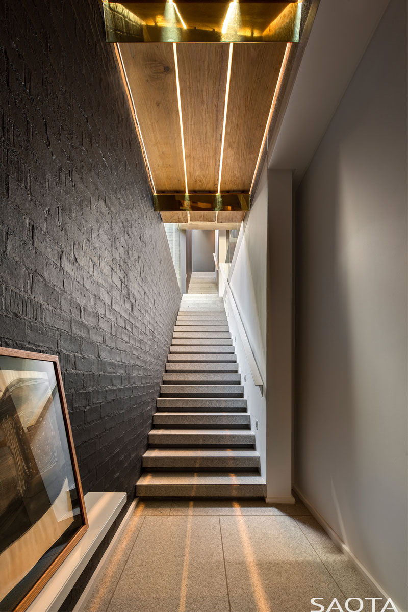 This modern staircase has a black accent wall and overhead lighting. #Stairs #Staircase