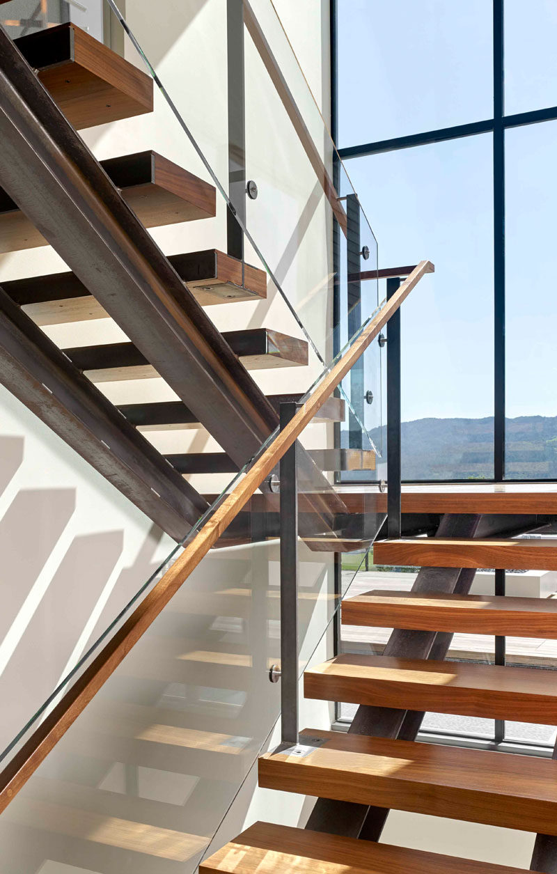 Steel and wood stairs with a glass handrail lead up to the second floor of this modern house. #Stairs #StairDesign #ModernStairs
