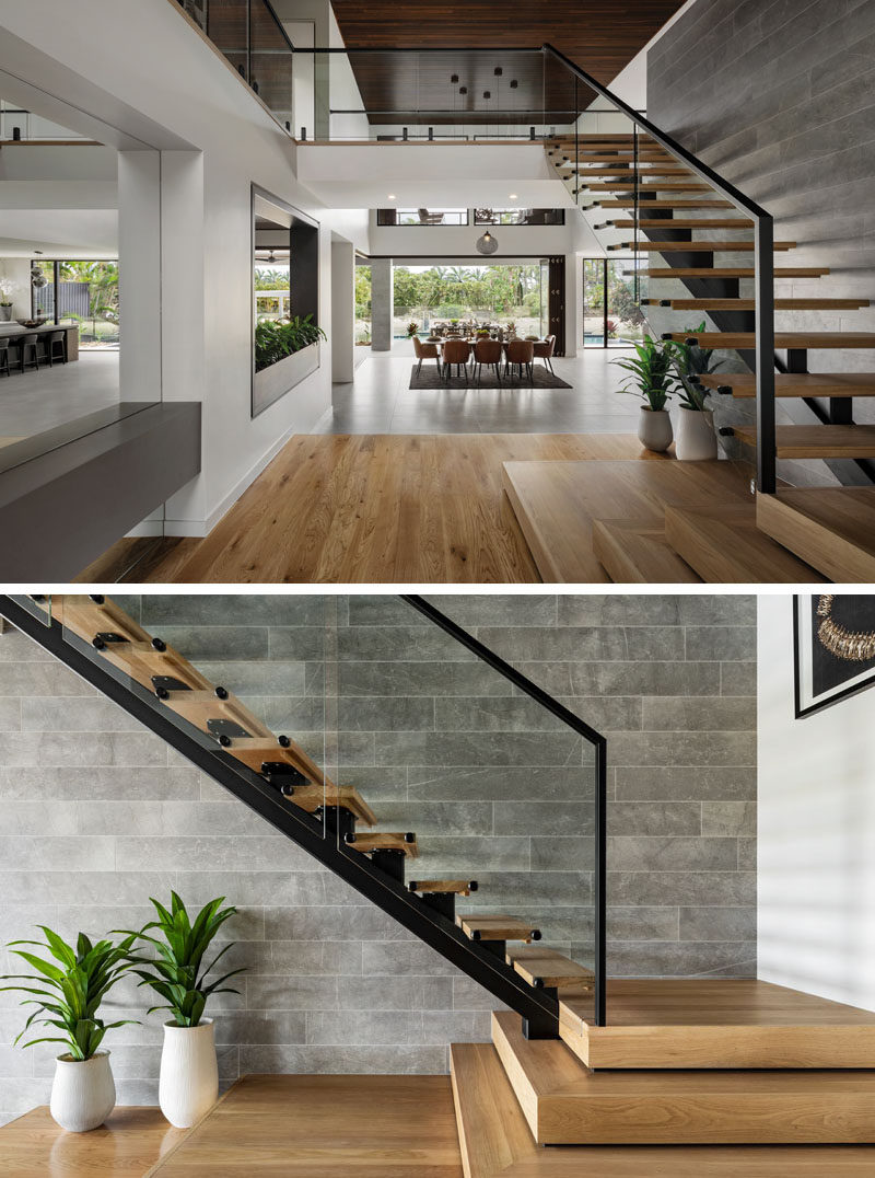Wood stairs with a steel frame lead up to the second floor against a tiled wall.