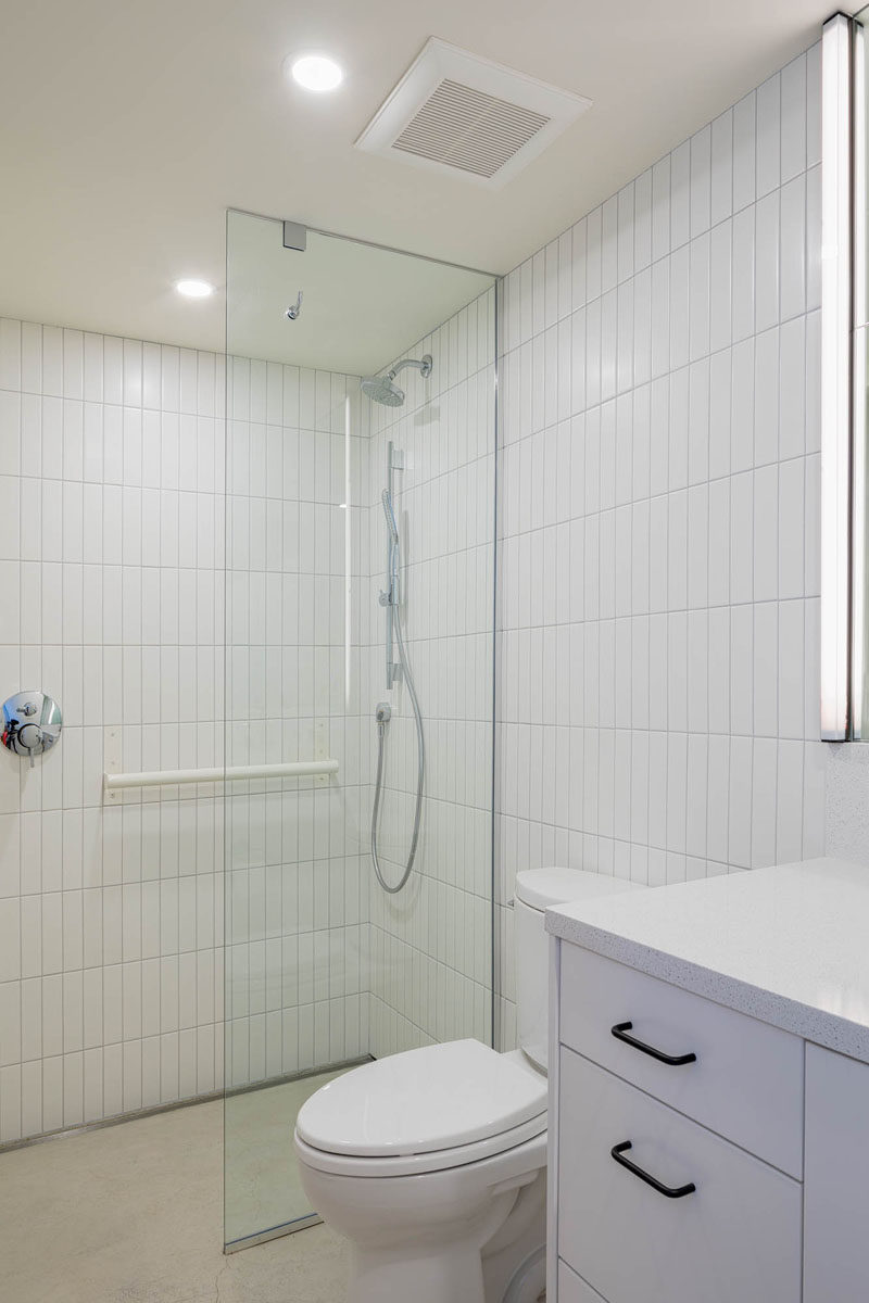 This white bathroom features a walk-in shower with a glass shower green, and rectangular white tiles in a vertical orientation. #WhiteBathroom