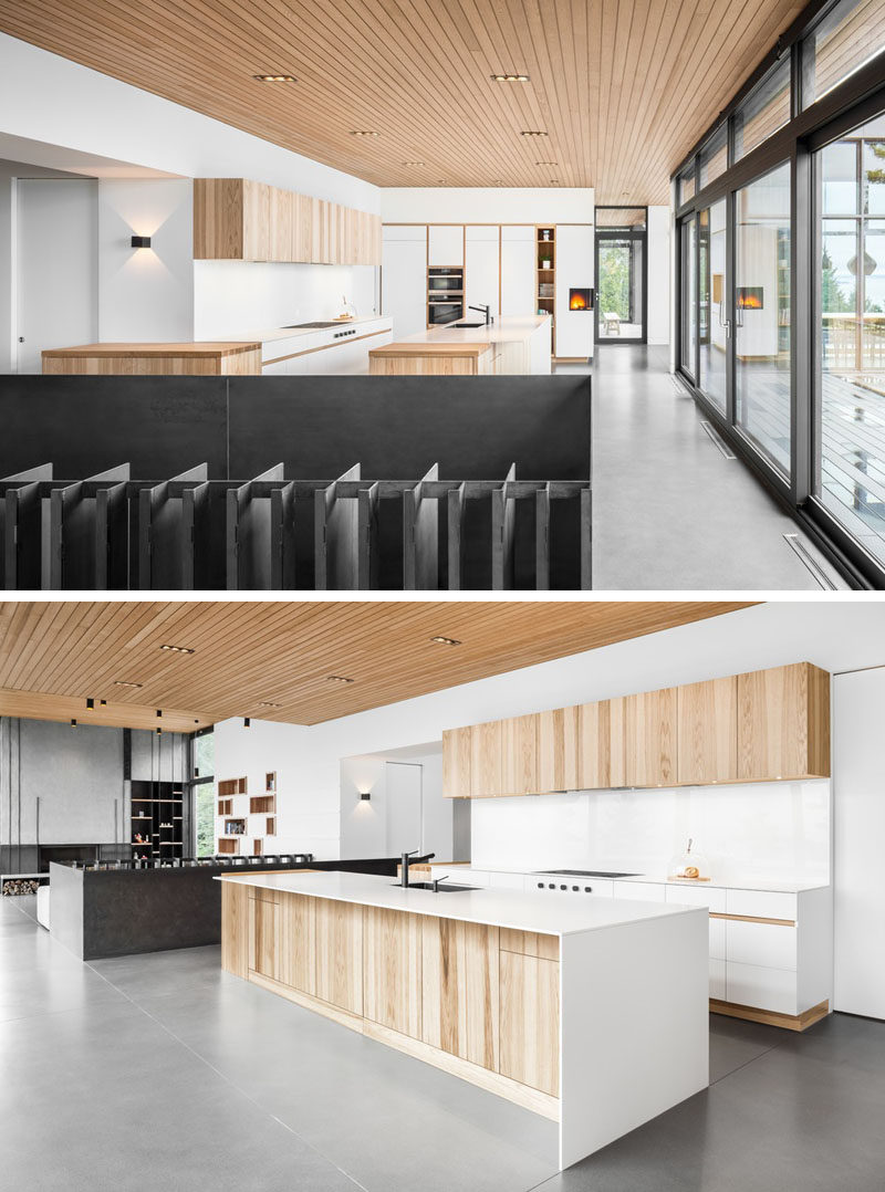 Floor-to-ceiling windows and sliding doors in this modern house, fill the interior with natural light, and in the kitchen, light wood cabinetry and design elements have been paired with white cabinetry for a contemporary appearance. #ModernKitchen #KitchenDesign #Windows