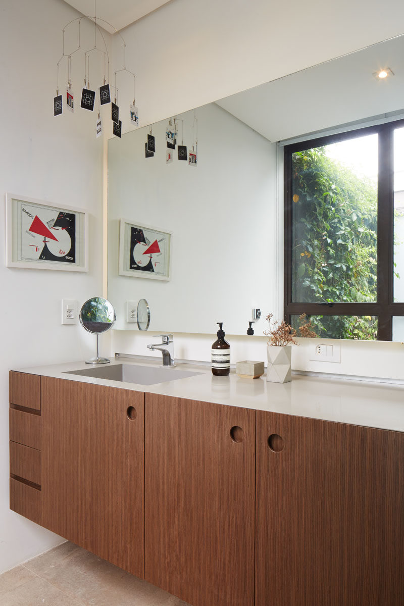 In this modern bathroom, there's a wood vanity with a light colored countertop, and a large mirror reflects a green wall outside. #BathroomDesign #ModernBathroom #WoodBathroomVanity