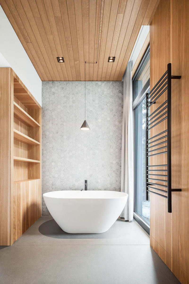 In this modern bathroom, a white freestanding bathtub sits in front of a grey-tiled wall. On one side, there's a shelving unit with storage, and on the other is a window with a curtain for privacy. #ModernBathroom #GreyTiledWall #BathroomDesign