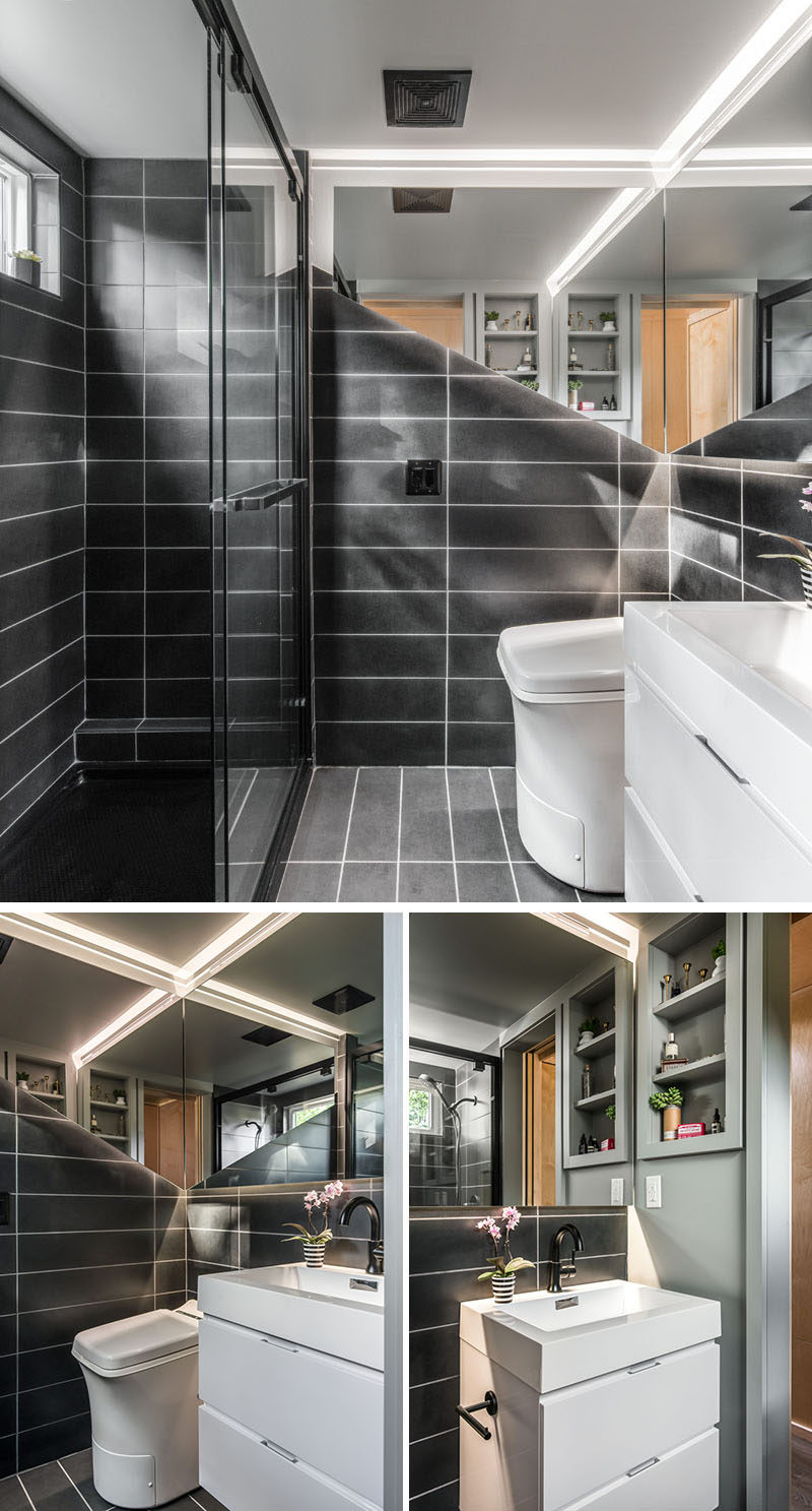 This small and modern bathroom in a tiny house, is covered in custom tile and features a floating mirror with valance LED lighting. There's also a custom floating vanity sink, a Cinderella incinerator toilet, and a 4'x6' full size shower. #Bathroom #BathroomDesign