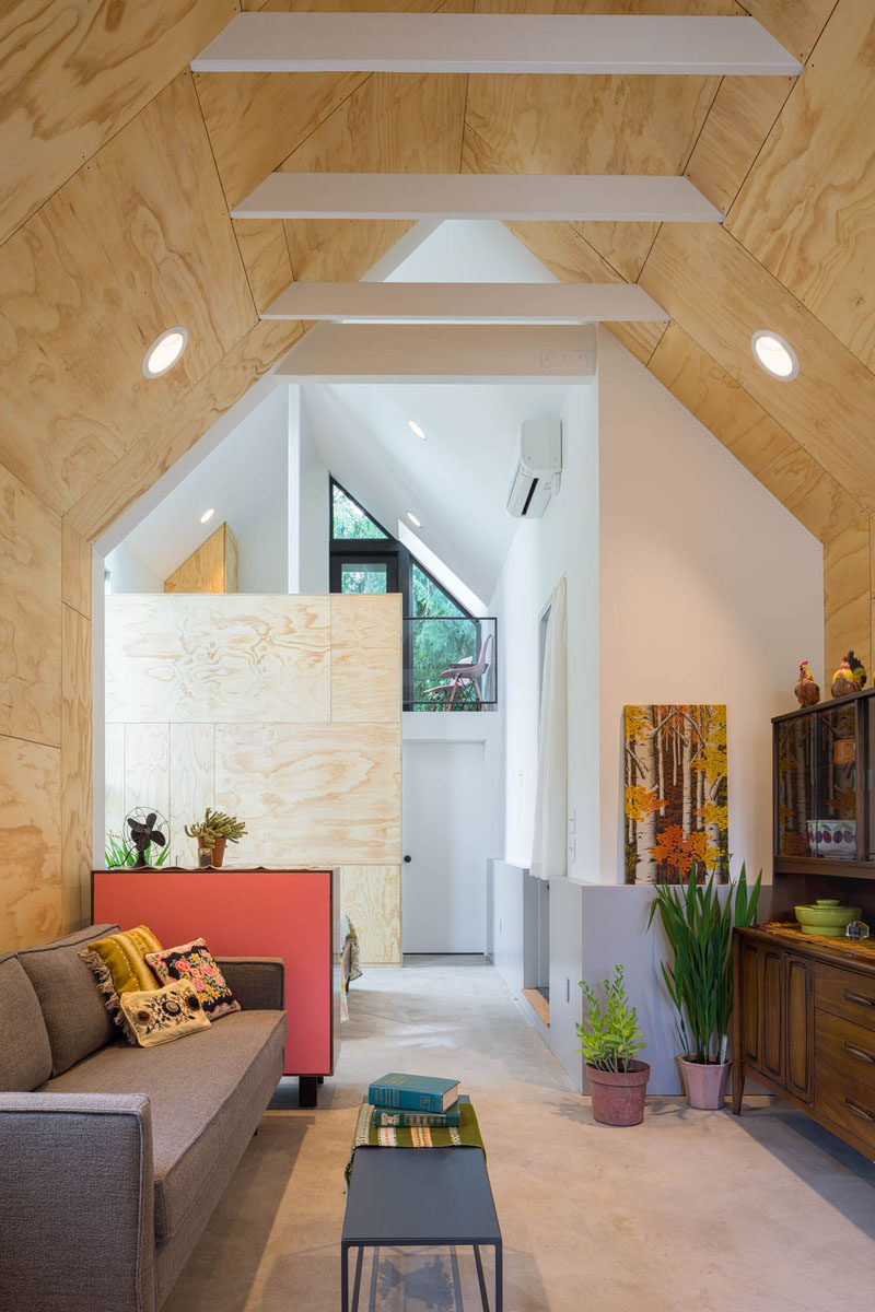 This tiny house features an open floor plan, a high pitched ceiling with exposed white rafters, and a loft area. #TinyHouse #InteriorDesign #Architecture