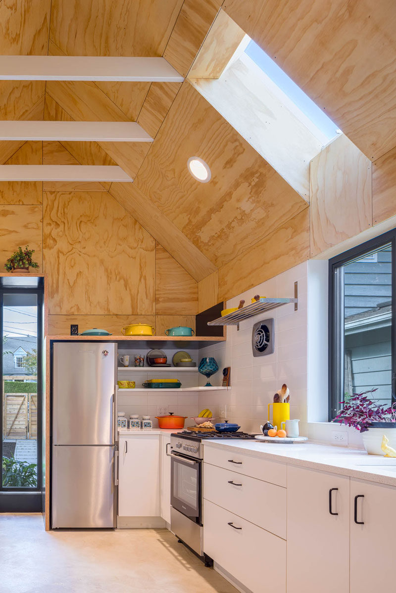 The interior of this tiny house features custom plywood panel walls, polished concrete flooring, and a full-size kitchen. #TinyHouse #SmallLiving #KitchenDesign