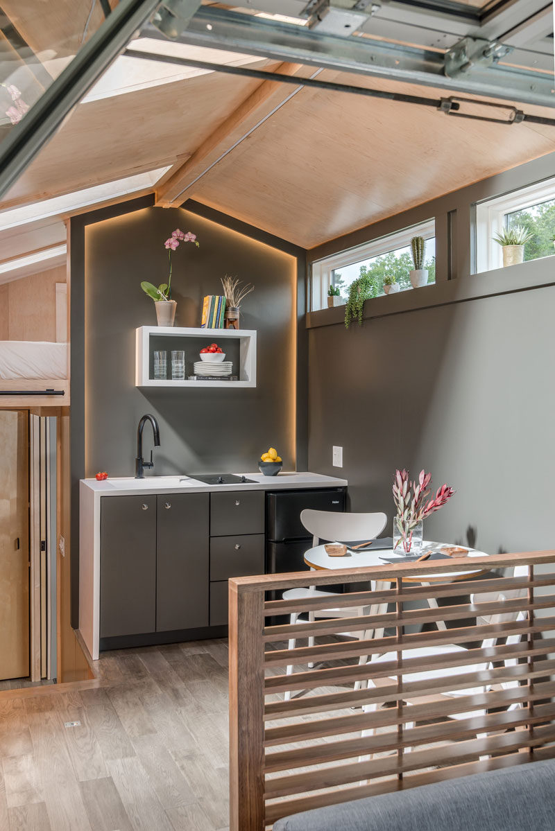 In the kitchen of this tiny house, there's a small sink, cooktop, fridge and small amount of storage. Hidden lighting gives the kitchen a soft glow. #TinyHouse #TinyHome #TinyKitchen
