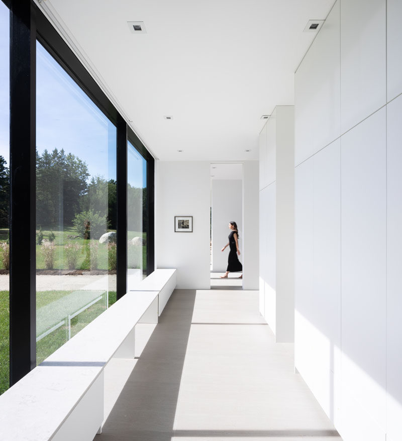 This modern hallway is lined with storage closets and benches positioned beside the floor-to-ceiling windows. #Hallway #ModernInterior #GlassWall