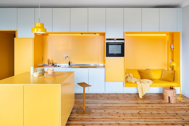 This renovated 1920s apartment in Stockholm received a modern makeover, with a custom designed wall that includes yellow built-in sections that house a kitchen and a seating nook. #InteriorDesign #Kitchen #SeatingNook