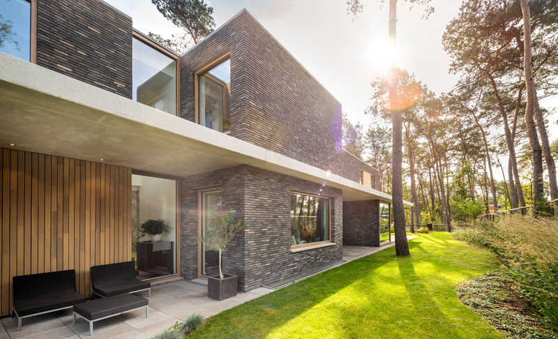 The exterior of this modern house features brick volumes that are separated by a concrete canopy, providing a strong horizontal line to the vertical nature of its surroundings. #ModernHouse #Brick #Concrete #Architecture