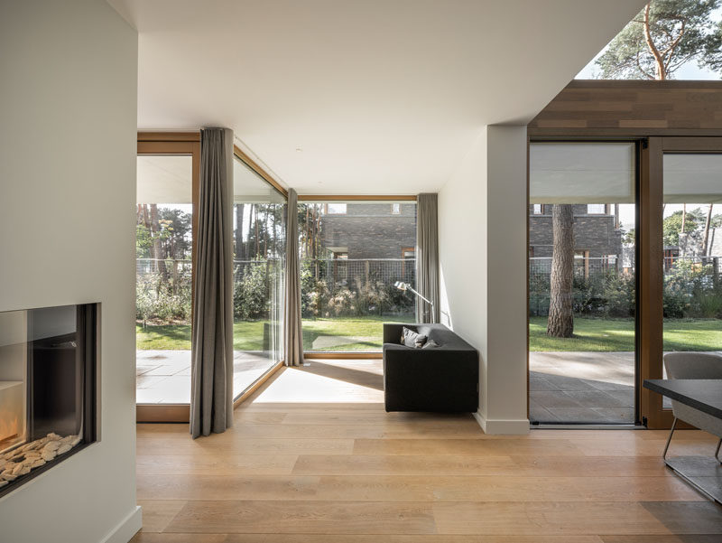 The interior of this modern house is built up of linked volumes of different sizes which create a series of pockets, like this sitting area. #FloorToCeilingWindows #SittingRoom