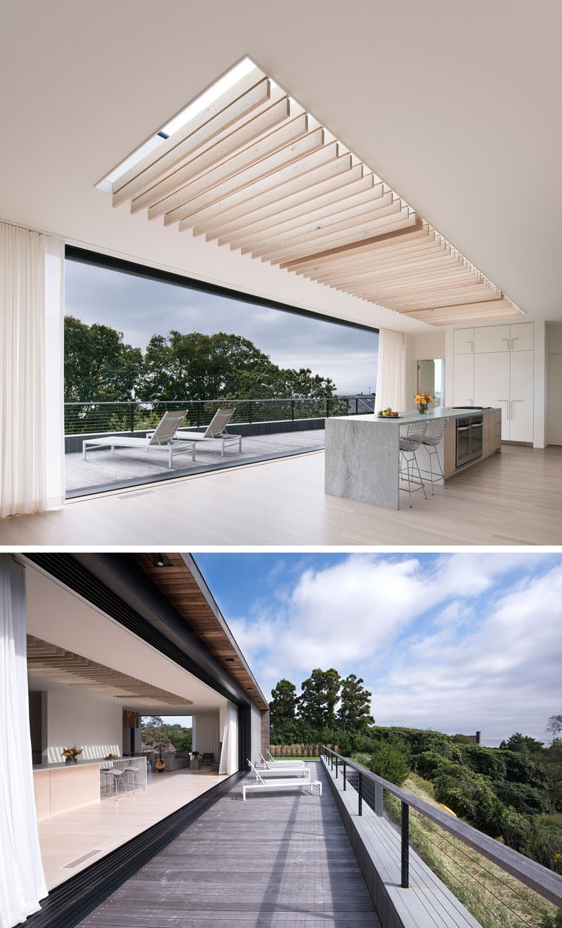 A large retracting glass wall connects the interior of this modern house with the outdoor spaces, enabling ocean views, breezes, and natural lighting to filter through. #ModernHouse #Skylight #InteriorDesign
