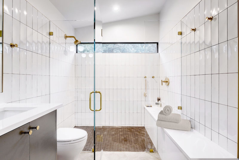 In this modern bathroom, white glossy tiles cover the walls, while a glass shower screen allows natural light from the window to filter through to the rest of the bathroom. #Bathroom #ModernBathroom #BathroomDesign