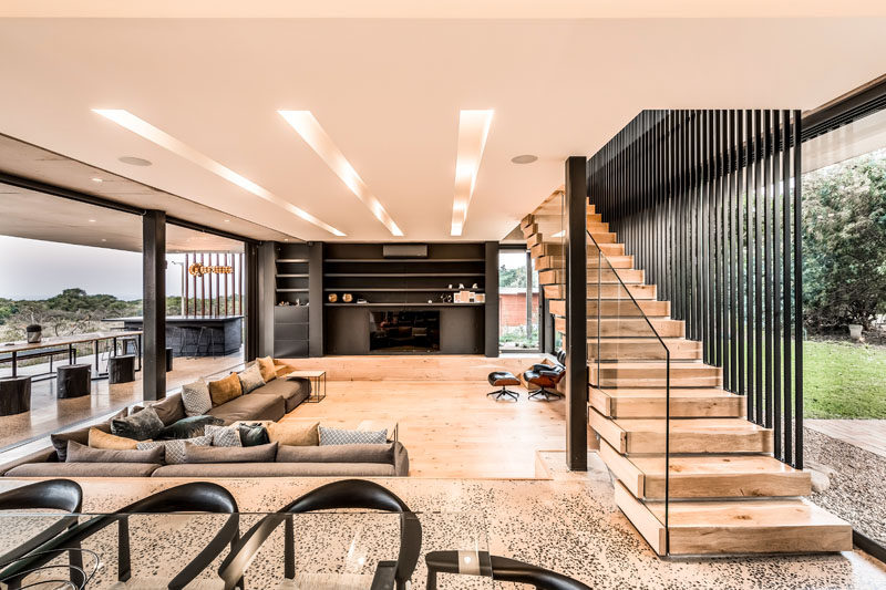 This modern house has a sunken living room with a large corner couch that sits flush with the floor that surrounds it. #SunkenLivingRoom #LivingRoom #OpenPlanInterior