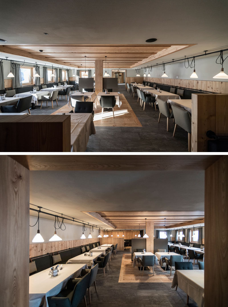 In the modern restaurant, banquette seating lines the walls, while simple lighting highlights each table. #Restaurant #RestaurantDesign