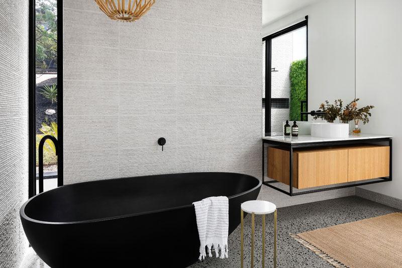 In this modern bathroom, a matte black freestanding bathtub complements the black detailing on the vanity and the window frames. #ModernBathroom #BlackBathtub #InteriorDesign