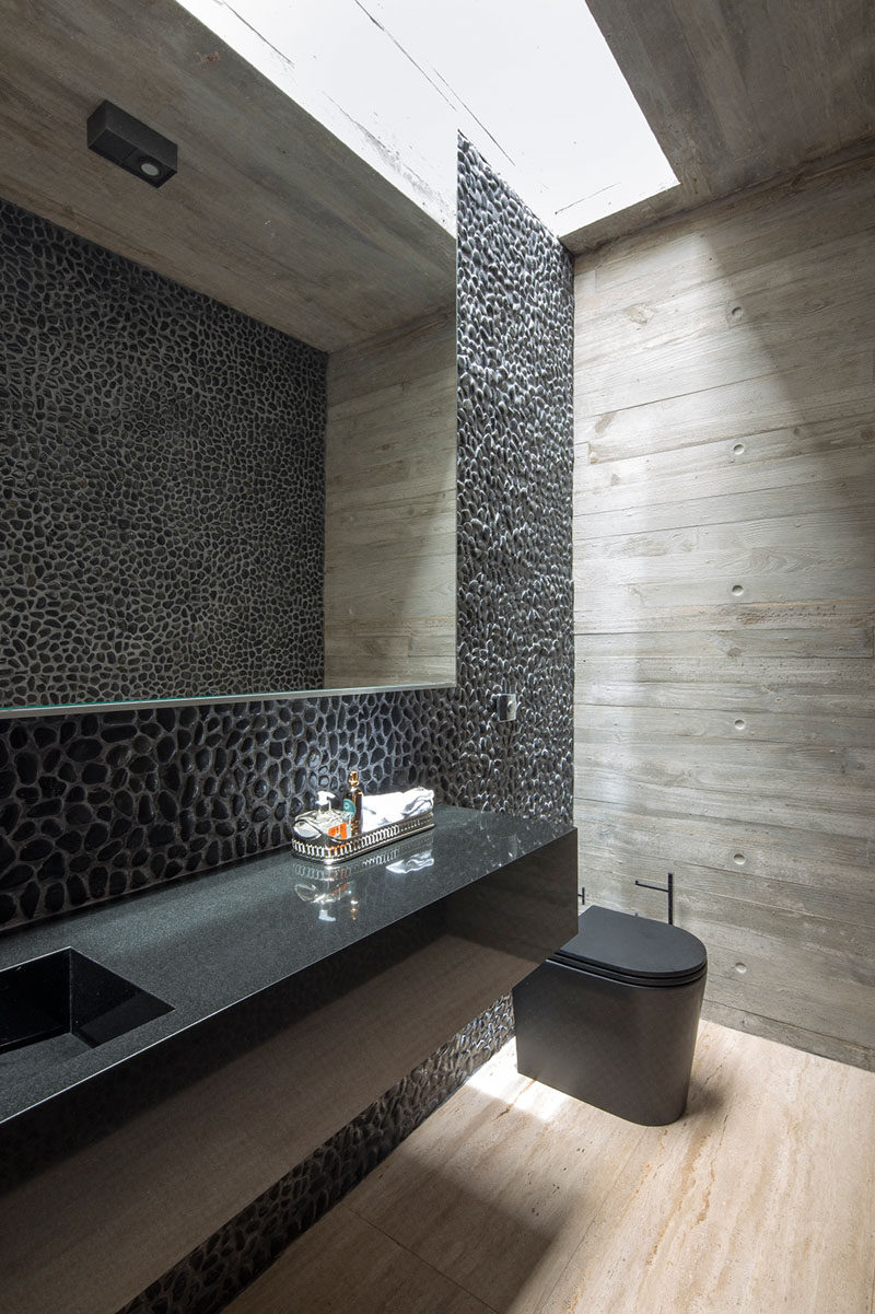 In this modern master bedroom, a feature wall of pebbles with a mirror reflects the pebbles on the opposite wall, while a skylight provides extra light to the room. #ModernBathroom #BathroomDesign