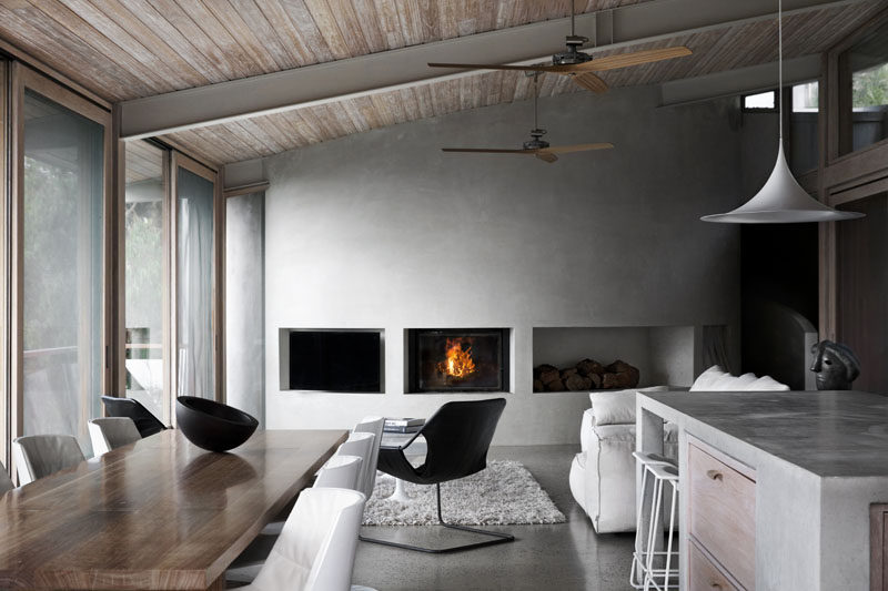In this modern living room, a curved concrete wall has built-in areas for a television, fireplace, and wood storage. #LivingRoom #CurvedConcreteWall #Fireplace
