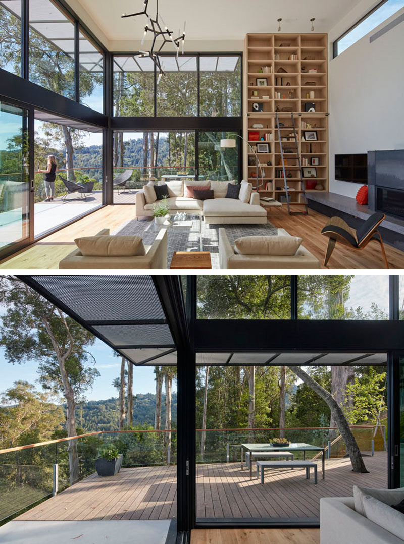 In this modern living room, double height ceilings make the living room feel large and open, with walls of windows showing off the views, while a floor-to-ceiling wood bookcase provides a place to display personal items. #LivingRoom #Shelving #GlassWalls
