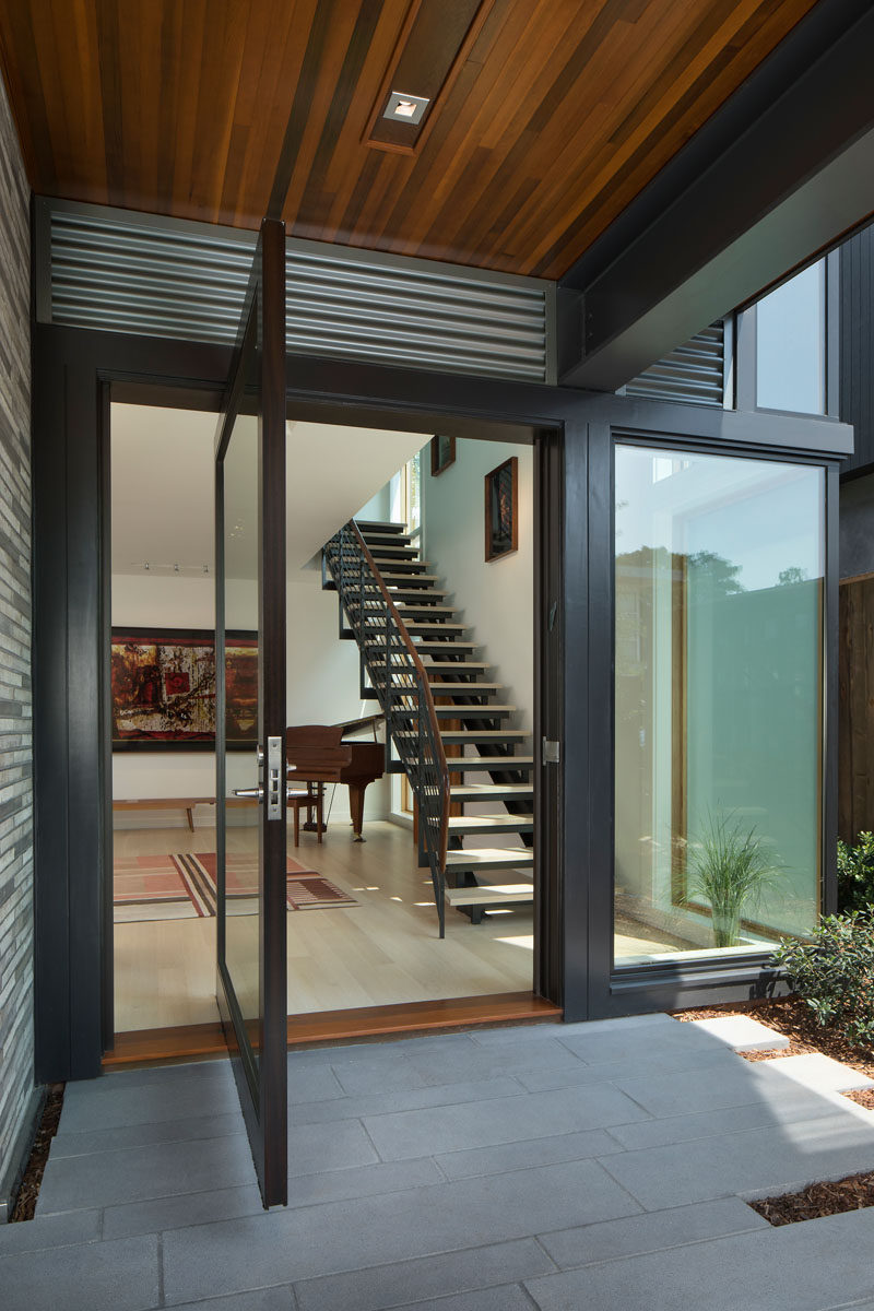 A large glass pivoting front door welcomes visitors to this modern house. #PivotingFrontDoor #FrontDoor