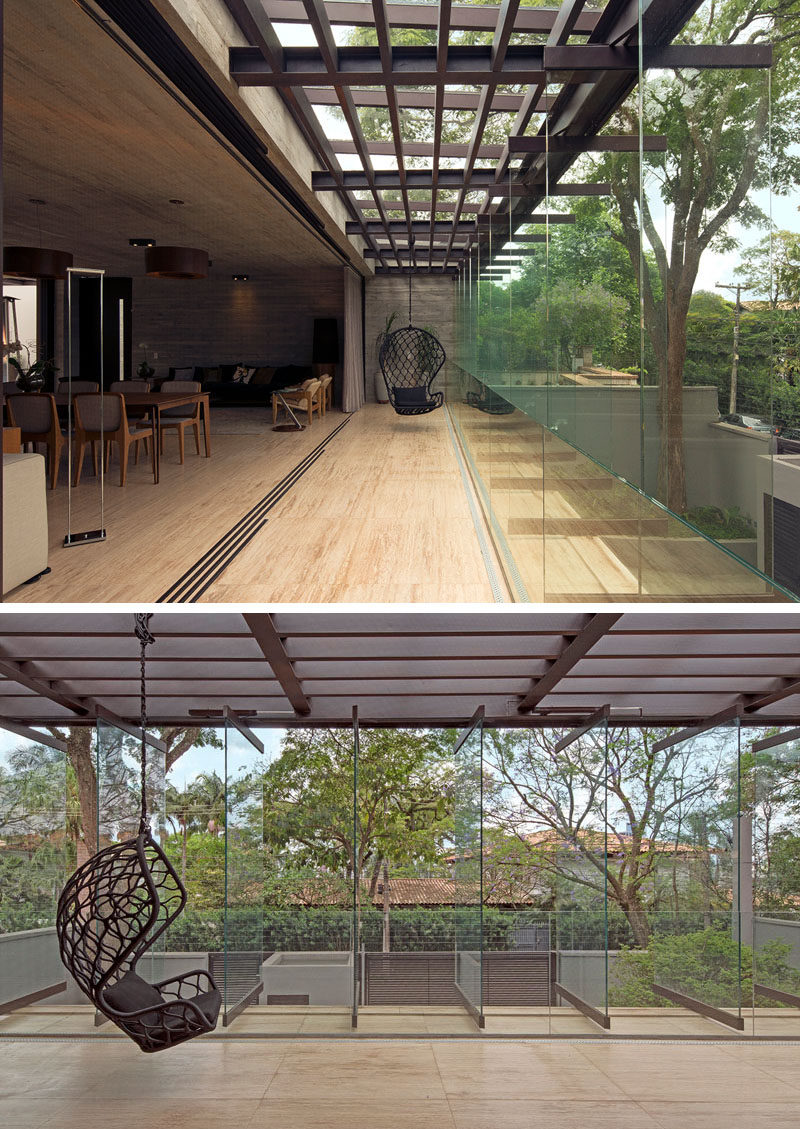 A large retractable wall connects the interior to a semi-outdoor space, that has pivoting glass panels that can be opened or closed depending on the weather. #Windows #ModernHouse