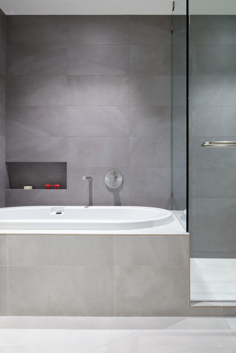 In this modern bathroom, the bathtub has been built-in and large grey tiles that contrast the white bathtub, cover the walls and bathtub surround. #GreyBathroom #ModernBathroom #BuiltInBathtub