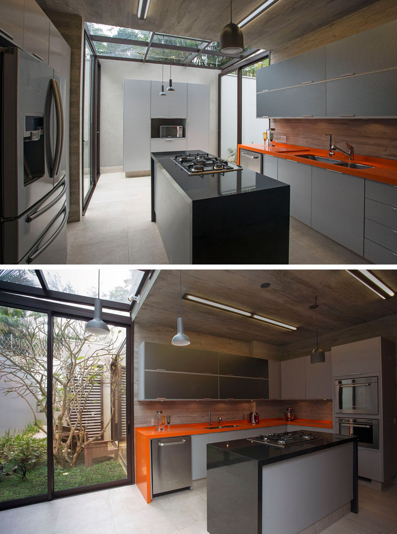In this modern kitchen, a section of the ceiling has been made from glass, allowing for natural light to filter through, while a sliding glass door opens up to a small courtyard with seating. #ModernKitchen #KitchenDesign