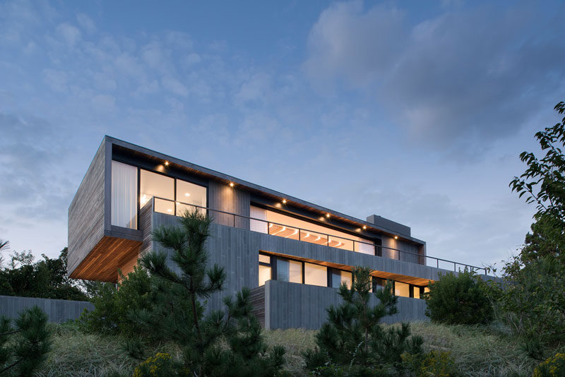 Naturally-weathered horizontal mahogany decking spans between the locally sourced bluestone walls and alternates as a covering for the roofs, walls, floors, and ceilings of the inhabited spaces of this modern house. #Architecture #HouseDesign #WoodSiding