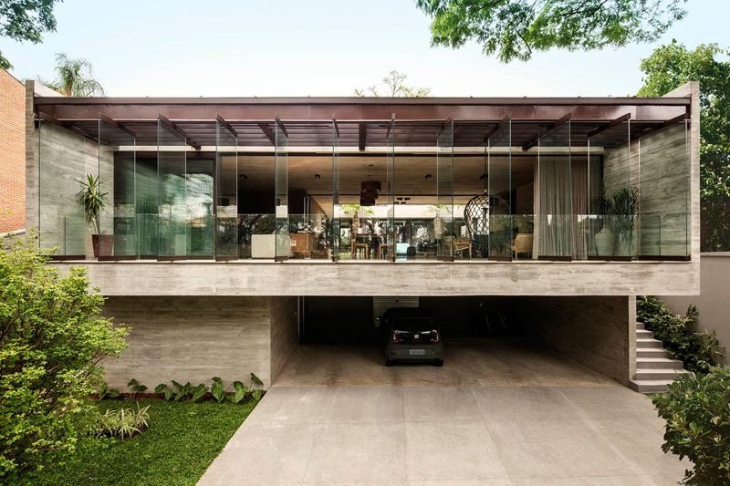 Drucker Architecture have recently completed a modern concrete house in Cidade Jardim, Brazil, that sits on a slope, and wraps around a grassy courtyard and a swimming pool. #Architecture #ConcreteHouse #ModernHouse
