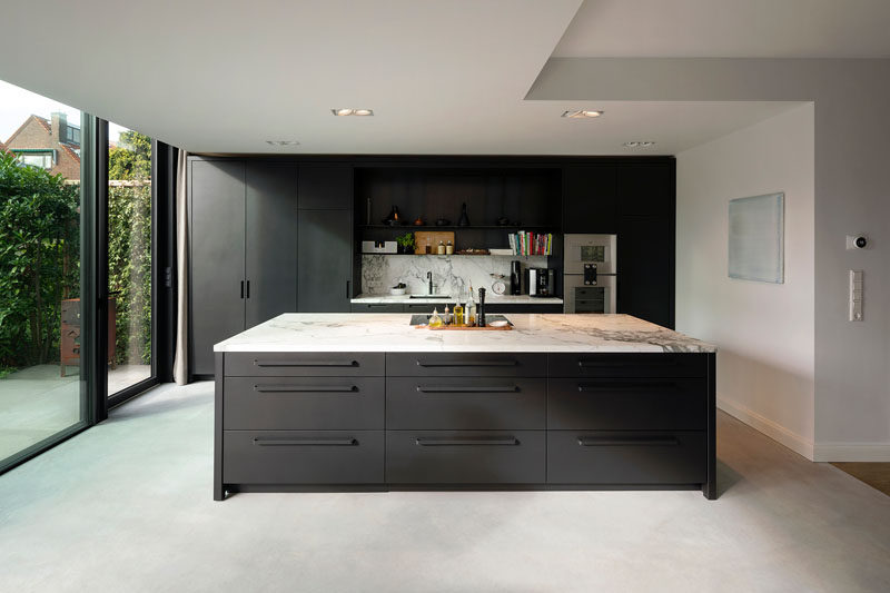 A new kitchen was created inside this modern house extension, and the dark cabinetry is a strong contrast to the white walls, ceiling, and light concrete floor. #ModernKitchen #DarkCabinetry #DarkKitchen #ConcreteFloors