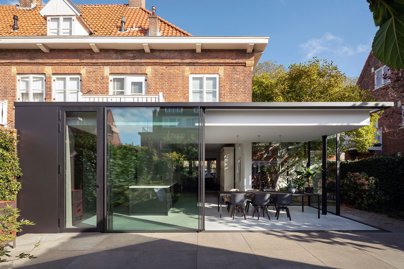 Bloot Architecture have designed a minimalist house extension in The Netherlands, that contrasts the brick architecture of a 1927's house. #GlassWalls #ModernHouseExtension #Architecture