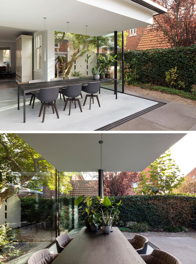 When the glass walls of this modern house extension are open,the home owners now have a semi-enclosed outdoor space that allows them to enjoy the back garden. #DiningRoom #ModernHouseExtension #GlassWalls
