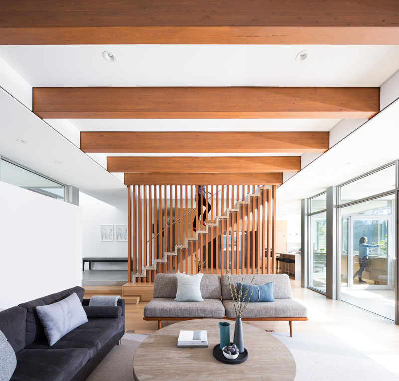 "The living room in this modern house has a ceiling that's composed of exposed 5""x12"" stained Douglas Fir glulam beams that extend outward to create a covered patio deck. #Ceiling #Beams #WoodBeams #LivinRoom"