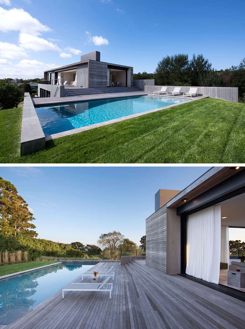 The interior spaces of this modern house open to a deck, which steps down to the swimming pool and grassy lawn. #Deck #ModernHouse #SwimmingPool