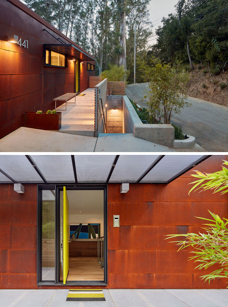 The exterior of this modern house is covered in weathering steel, and over time, the steel will continue to oxidise. A bright yellow pivoting front door welcomes guests to the house. #WeatheringSteel #Siding #Architecture #FrontDoor #PivotingDoor