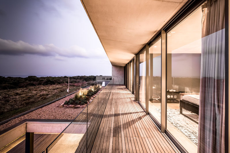 A long balcony runs the length of this modern home's upper floor, and provides views of the surrounding area and the small garden on the roof of the lower level. #Balcony #Architecture