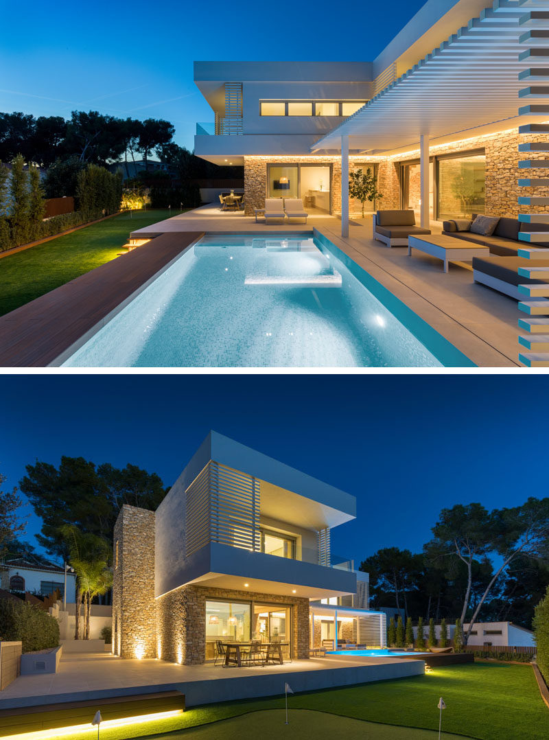 The first floor of this modern house appears to rest on the stone base, and provides cover for some of the outdoor areas of the main floor of the home, like the outdoor dining area. #ModernHouse #ModernArchitecture