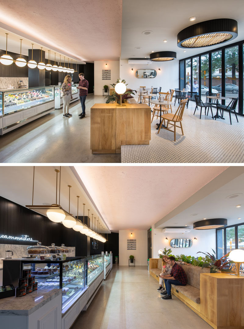 Inside this cafe, a split level creates designated areas for seating and ordering. Floor-to-ceiling folding glass doors can be opened to connect the seating area to the patio outside, while on the lower level, a long couch gives people a place to wait for their order. #Cafe #RetailDesign #Seating