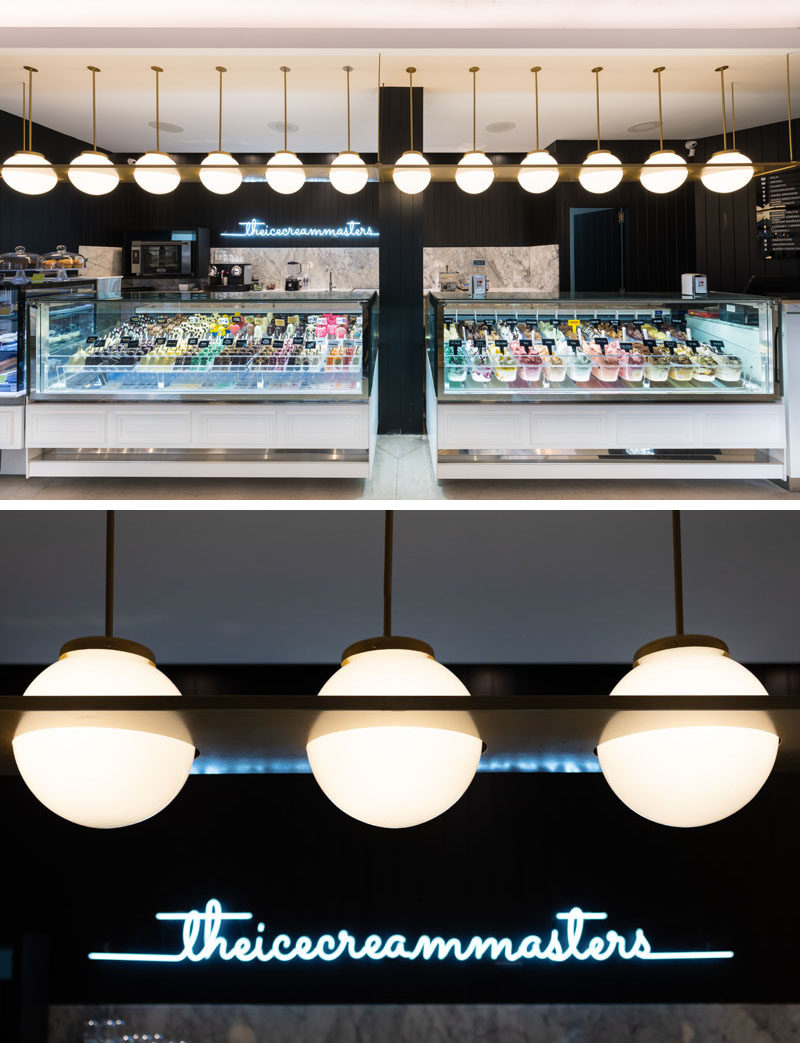 Lighting above the ice cream display draws the customers eye in this cafe, while a neon light sign brightens up the black wall. #Lighting #RetailDesign