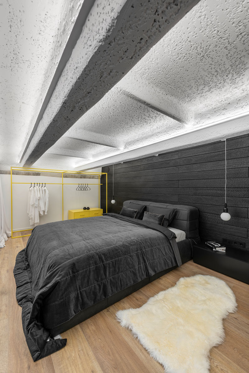 In this modern loft bedroom, soft white curtains can be closed for privacy, while the contrasting accent wall behind the bed is covered by burnt Accoya wood. A pop of yellow has also been added in the form of a freestanding open closet. #ModernBedroom #BlackAccentwall #BurntWoodWall