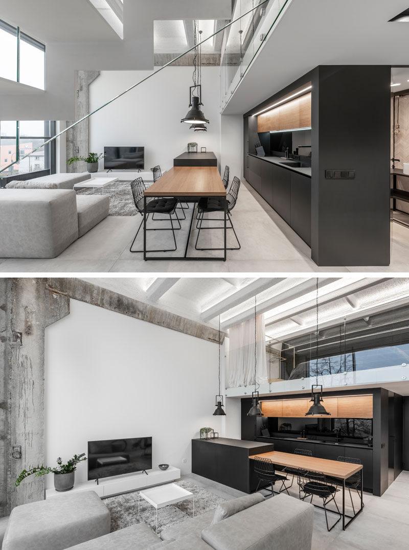 Tách biệt phòng khách và nhà bếp trong căn hộ gác xép hiện đại này, là một hòn đảo thả xuống để trở thành bàn ăn gỗ cho bốn người. #DiningTable #BlackK Kitchen #InteriorDesign
