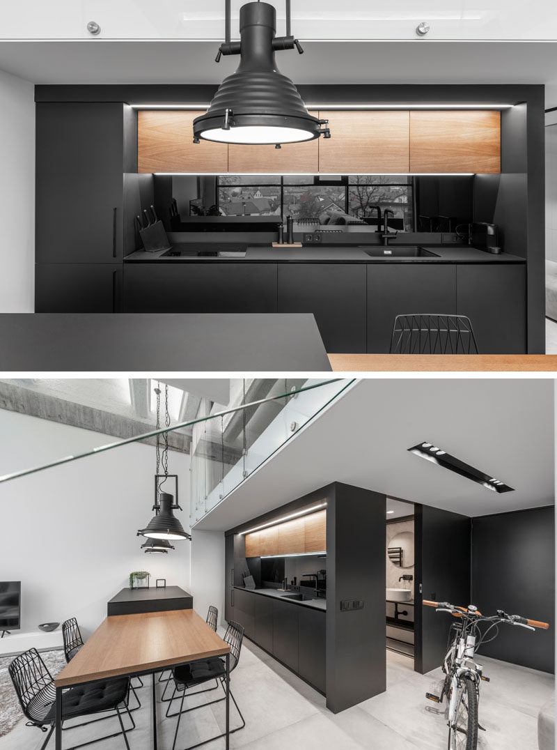 In this modern kitchen, the upper wood cabinetry complements the dining table, contrasts the black cabinets, and adds a natural touch to the minimalist interior. #ModernKitchen #BlackKitchen