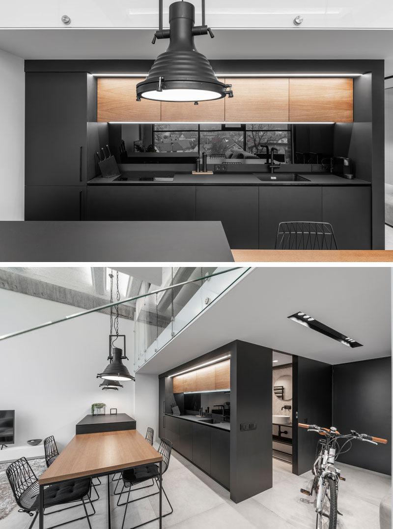 Trong nhà bếp hiện đại này, tủ gỗ phía trên bổ sung cho bàn ăn, tương phản với tủ màu đen và thêm một nét tự nhiên cho nội thất tối giản. #ModernK Kitchen #BlackK Kitchen