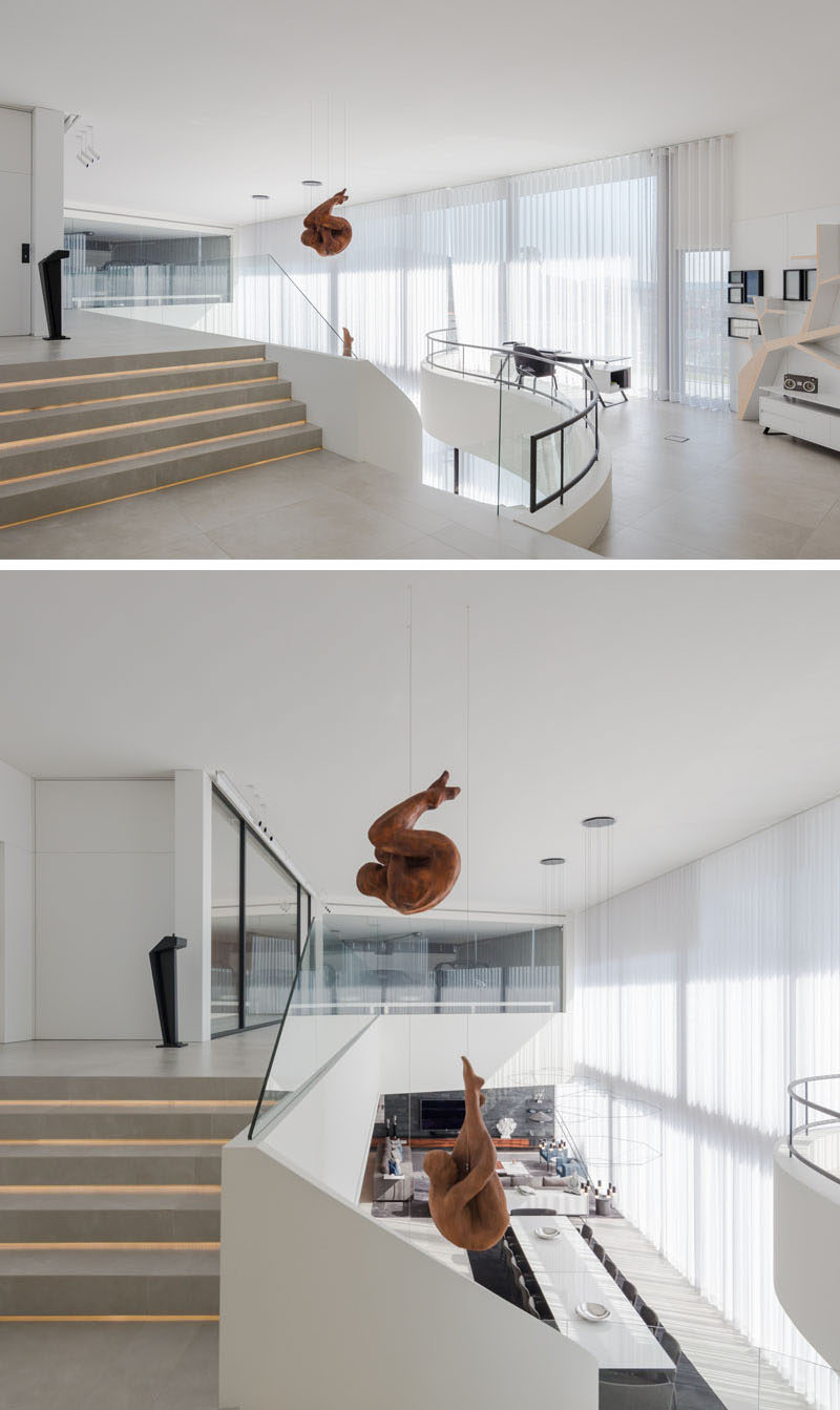 At the top of this modern curved staircase, there's a small area set up as a home office, that overlooks the sculptures and the dining area below. #HomeOffice #HangingSculptures